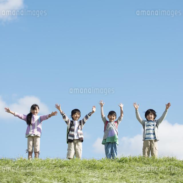 草原で両手を挙げる小学生の写真素材 [FYI04552056]