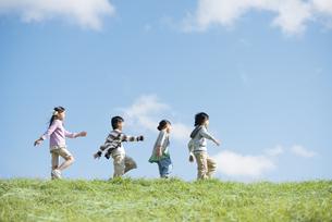 草原を歩く小学生の写真素材 [FYI04552071]