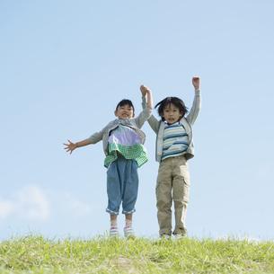 草原で手をつなぎジャンプをする小学生の写真素材 [FYI04552080]