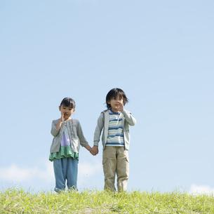 草原で手をつなぐ小学生の写真素材 [FYI04552081]