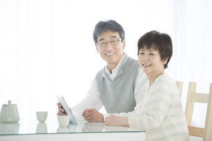 タブレットPCを持ち微笑むシニア夫婦の写真素材 [FYI04552092]