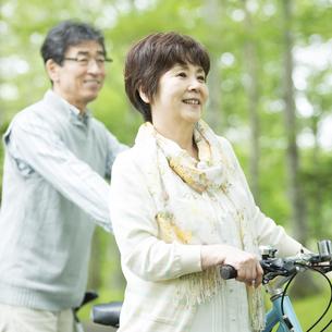 自転車を押すシニア夫婦の写真素材 [FYI04552125]