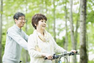 自転車を押すシニア夫婦の写真素材 [FYI04552126]