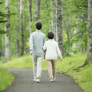 一本道を歩くシニア夫婦の後姿の写真素材 [FYI04552161]
