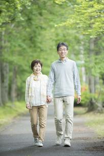 一本道を歩くシニア夫婦の写真素材 [FYI04552168]