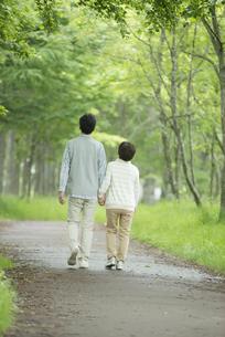 一本道を歩くシニア夫婦の後姿の写真素材 [FYI04552174]