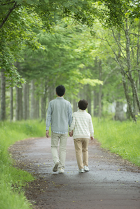 一本道を歩くシニア夫婦の後姿の写真素材 [FYI04552177]