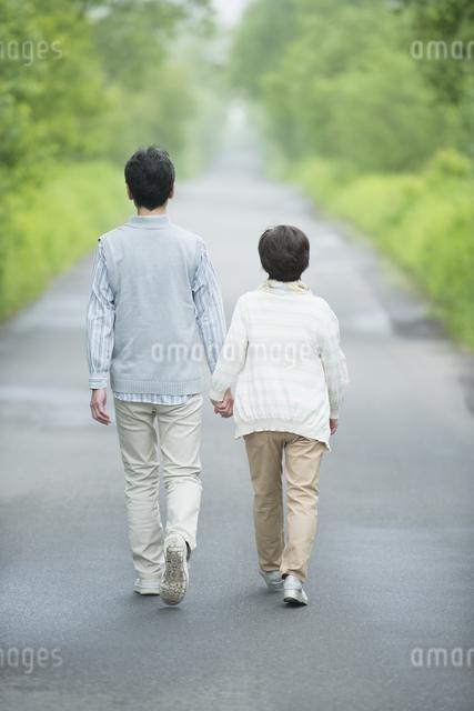 一本道を歩くシニア夫婦の後姿の写真素材 [FYI04552184]