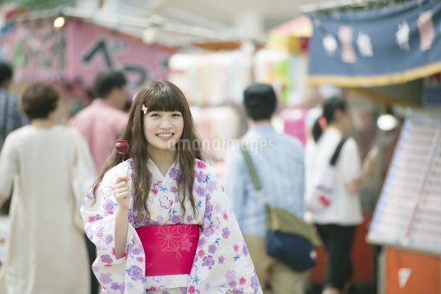 りんご飴を持ち微笑む女性の写真素材 [FYI04552206]