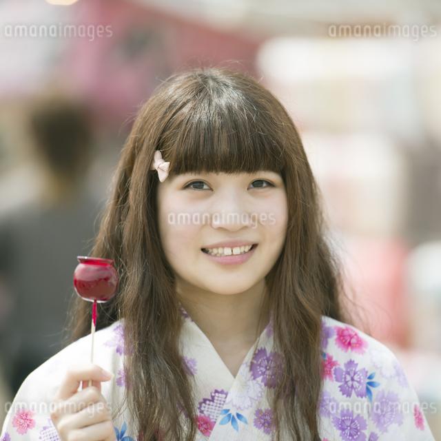 りんご飴を持ち微笑む女性の写真素材 [FYI04552209]