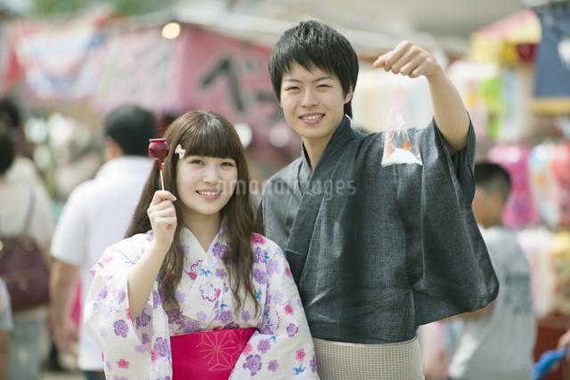 りんご飴と金魚の入った袋を持ち微笑むカップルの写真素材 [FYI04552214]