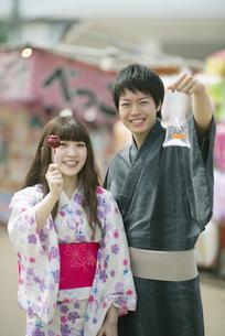 りんご飴と金魚の入った袋を持ち微笑むカップルの写真素材 [FYI04552215]