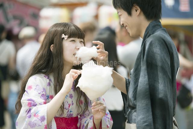 お祭りでわたあめを食べるカップルの写真素材 [FYI04552220]