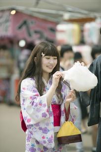 お祭りでわたあめを食べる女性の写真素材 [FYI04552226]