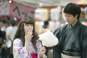 お祭りでわたあめを食べるカップルの写真素材 [FYI04552227]