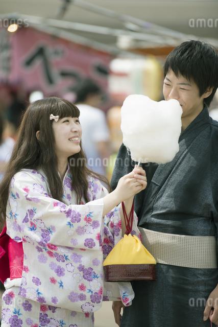 お祭りでわたあめを食べるカップルの写真素材 [FYI04552228]