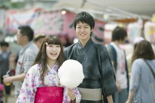 お祭りでわたあめを持ち微笑むカップルの写真素材 [FYI04552229]