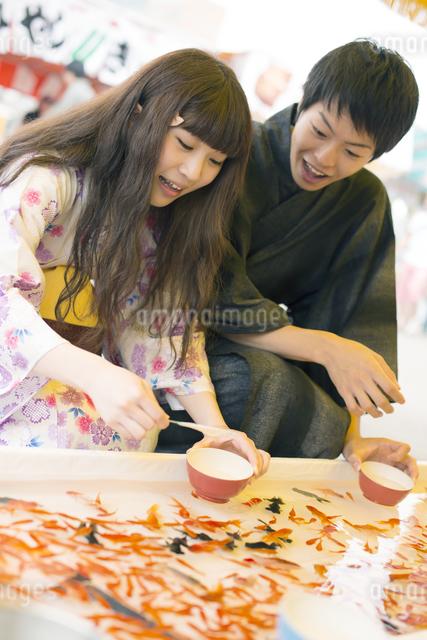 金魚すくいをするカップルの写真素材 [FYI04552240]