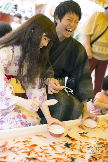 金魚すくいをするカップルの写真素材 [FYI04552242]
