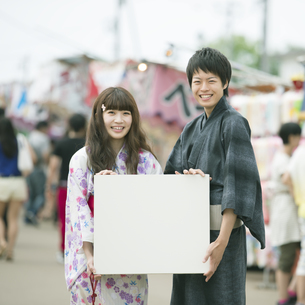 お祭りでメッセージボードを持ち微笑むカップルの写真素材 [FYI04552245]