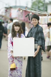 お祭りでメッセージボードを持ち微笑むカップルの写真素材 [FYI04552247]