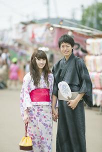 お祭りの屋台の前で微笑むカップルの写真素材 [FYI04552248]