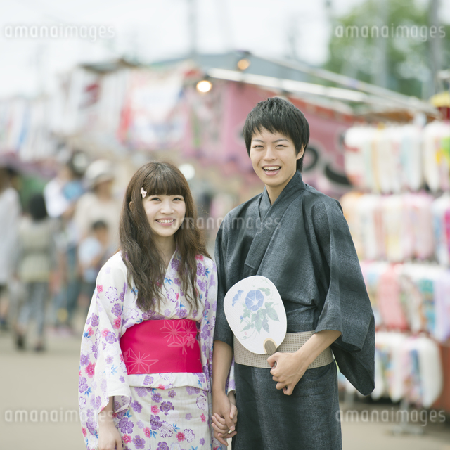 お祭りの屋台の前で微笑むカップルの写真素材 [FYI04552251]