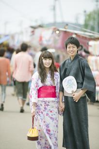 お祭りの屋台の前で微笑むカップルの写真素材 [FYI04552252]