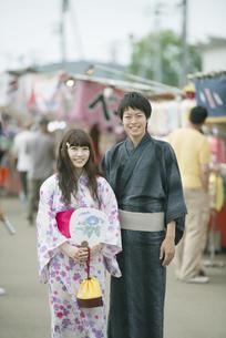 お祭りの屋台の前で微笑むカップルの写真素材 [FYI04552254]