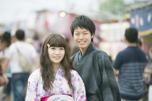 お祭りの屋台の前で微笑むカップルの写真素材 [FYI04552259]