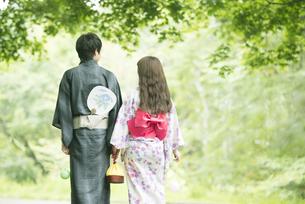 浴衣姿で手をつなぐカップルの後姿の写真素材 [FYI04552268]