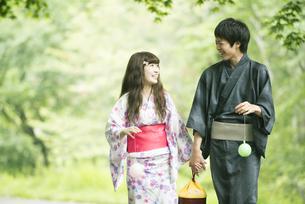 新緑の中を歩く浴衣姿のカップルの写真素材 [FYI04552277]
