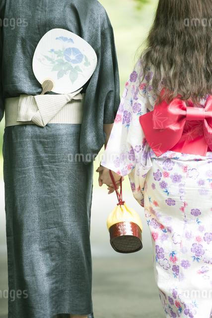 浴衣姿で手をつなぐカップルの後姿の写真素材 [FYI04552282]