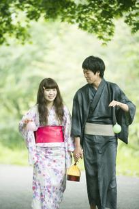 新緑の中を歩く浴衣姿のカップルの写真素材 [FYI04552283]