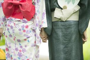 浴衣姿で手をつなぐカップルの後姿の写真素材 [FYI04552330]