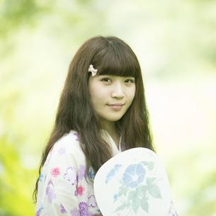 新緑の中で微笑む浴衣姿の女性の写真素材 [FYI04552342]