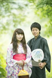 新緑の中で微笑む浴衣姿のカップルの写真素材 [FYI04552361]