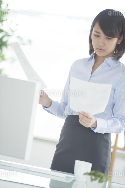 オフィスで書類を持つビジネスウーマンの写真素材 [FYI04552376]