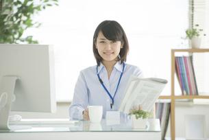 コーヒーカップと新聞を持つビジネスウーマンの写真素材 [FYI04552403]