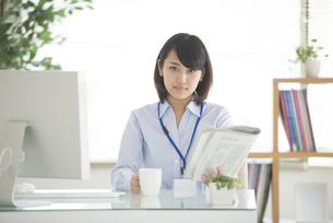 コーヒーカップと新聞を持つビジネスウーマンの写真素材 [FYI04552405]