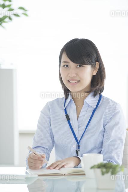 手帳に予定を書き込むビジネスウーマンの写真素材 [FYI04552434]