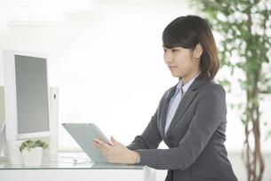 タブレットPCを操作するビジネスウーマンの写真素材 [FYI04552476]