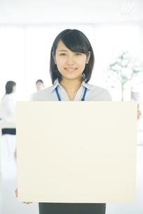 メッセージボードを持ち微笑むビジネスウーマンの写真素材 [FYI04552526]