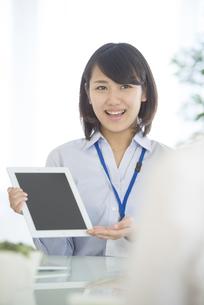 タブレットPCを持ち微笑むビジネスウーマンの写真素材 [FYI04552577]