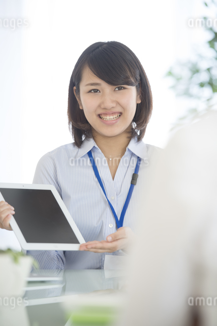 タブレットPCを持ち微笑むビジネスウーマンの写真素材 [FYI04552580]