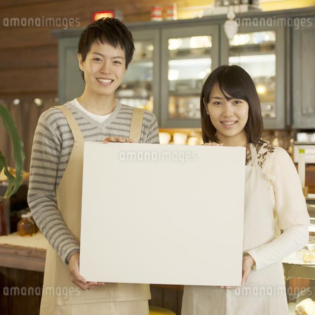 メッセージボードを持ち微笑むカフェの店員の写真素材 [FYI04552610]