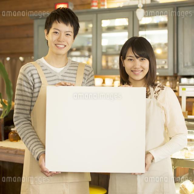 メッセージボードを持ち微笑むカフェの店員の写真素材 [FYI04552611]