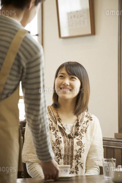 カフェで店員と話をする女性の写真素材 [FYI04552612]