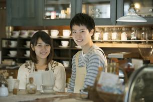 カウンターで微笑むカフェの店員の写真素材 [FYI04552623]