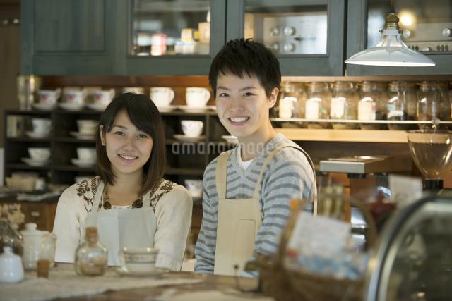 カウンターで微笑むカフェの店員の写真素材 [FYI04552624]